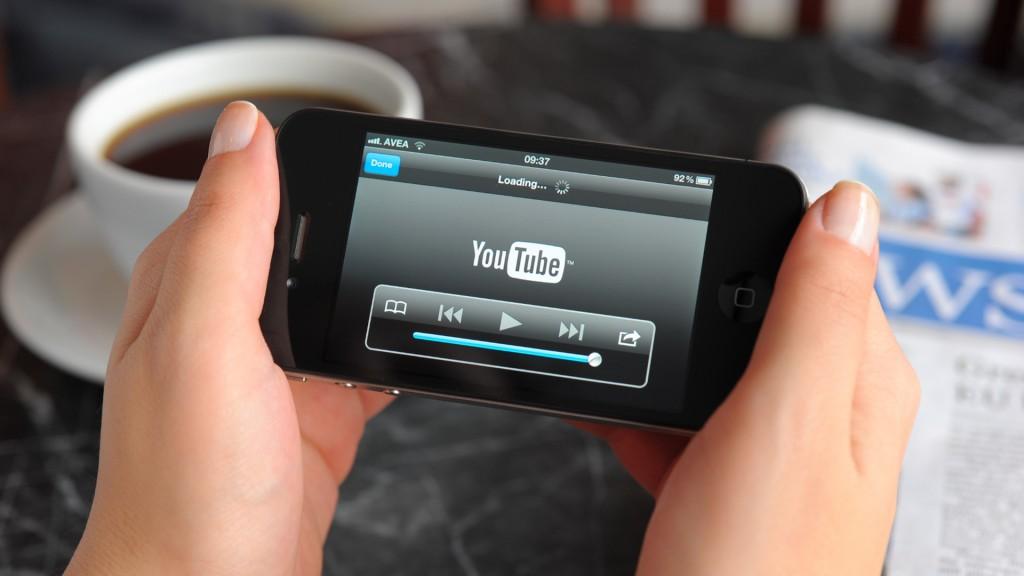 mãos de mulher seguram celular com tela do YouTube aberta