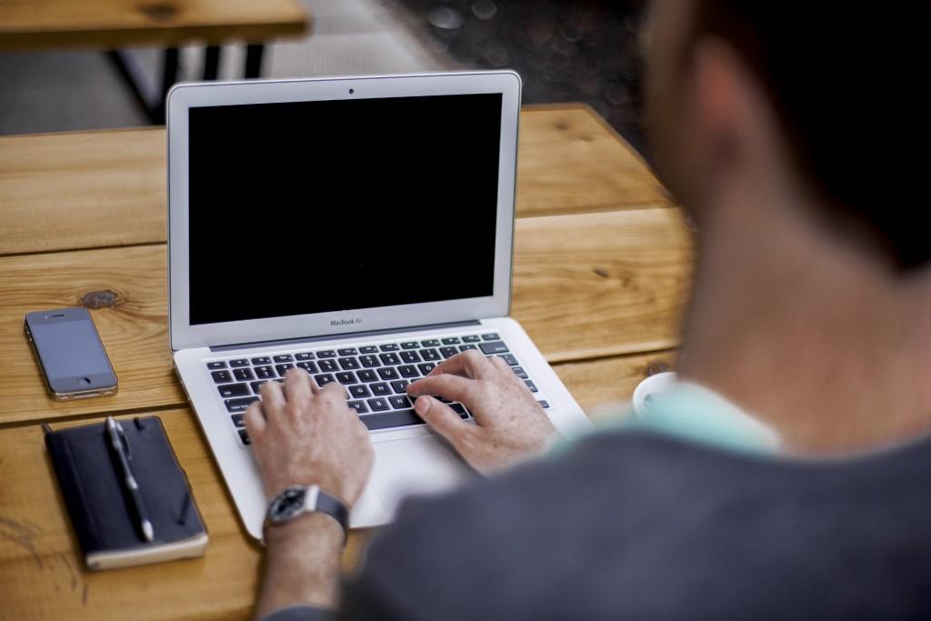 homem digitando num macbook